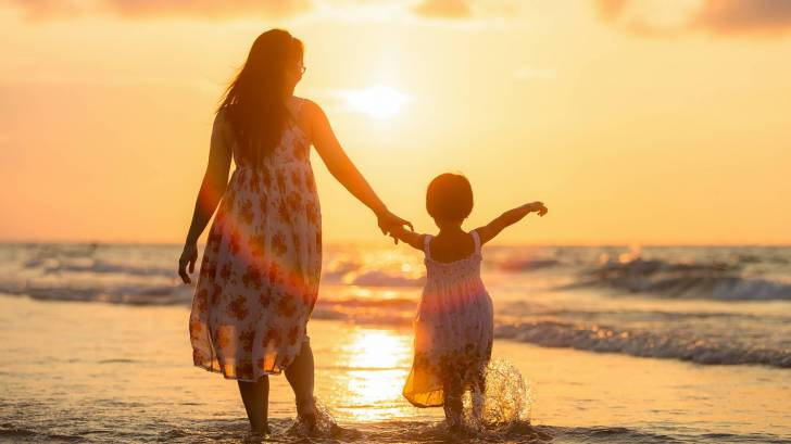 mother and young daughter on a beach walking