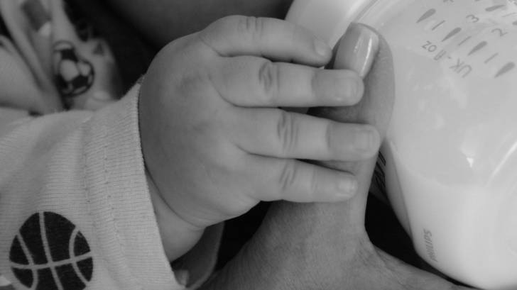 baby holding moms thumb while eating a bottle