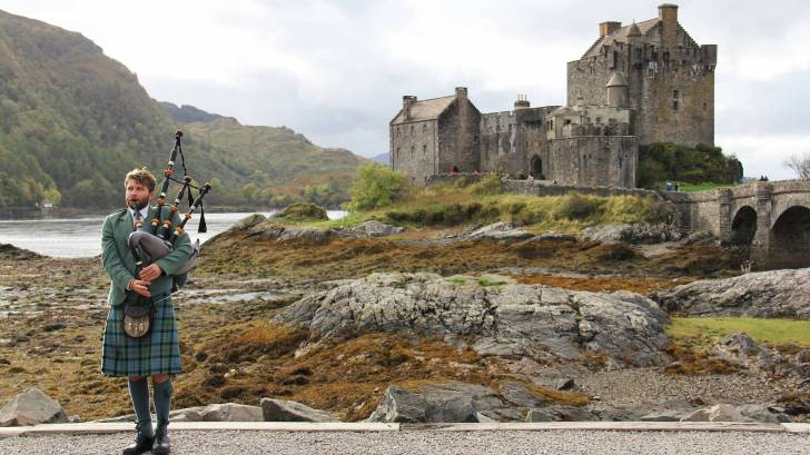 young man playing the bag pipes in the highlands