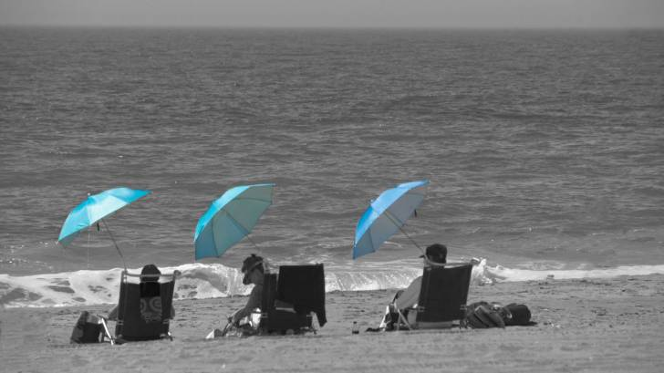 beach goers using umbrellas and hats to prevent sun burn