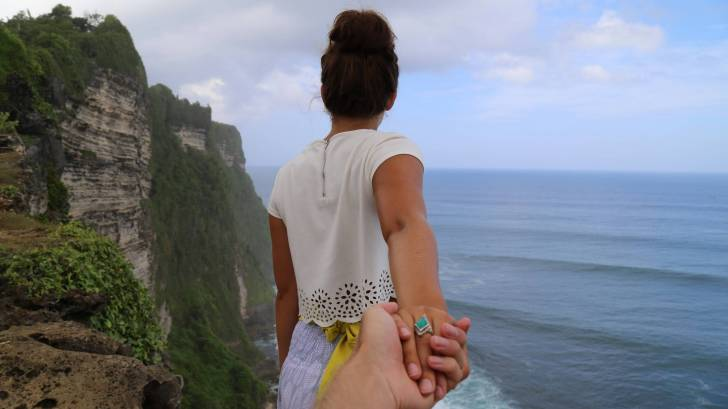 couple on the cliff overlooking the ocean, holding hands