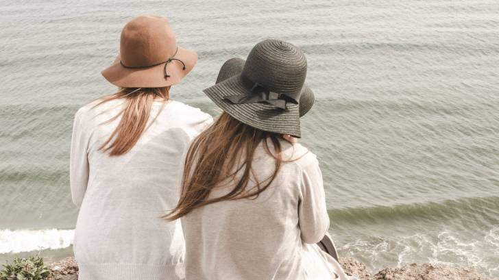two women sitting on the beach wearing hats, calm sea