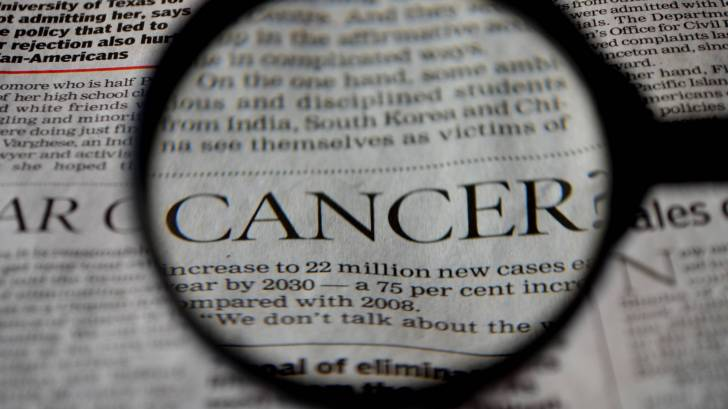 cancer word under a magnifying glass in a news paper