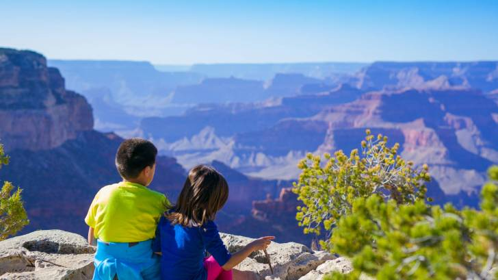 children sitting at the top of a canyon