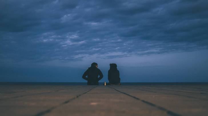 young couple sitting on the end of a dock talking at night