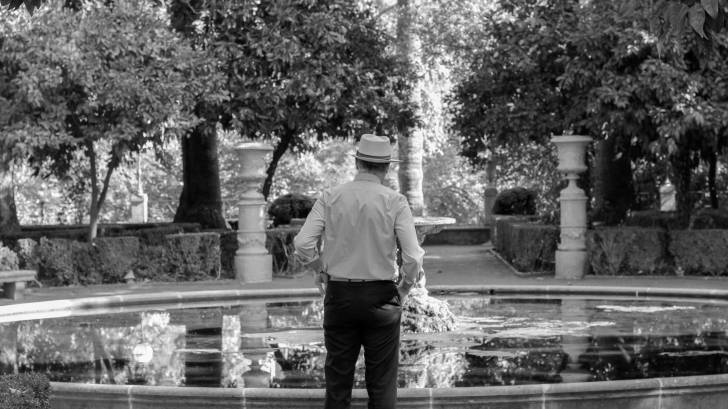 older man looking into a fountain