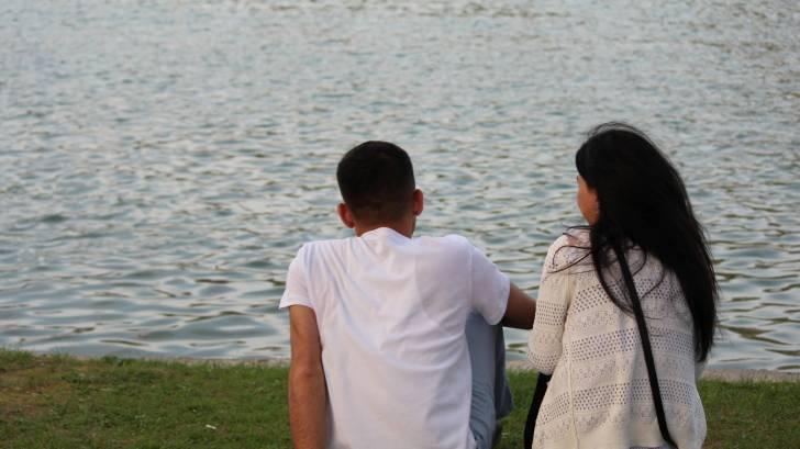 coupke sitting near a lake