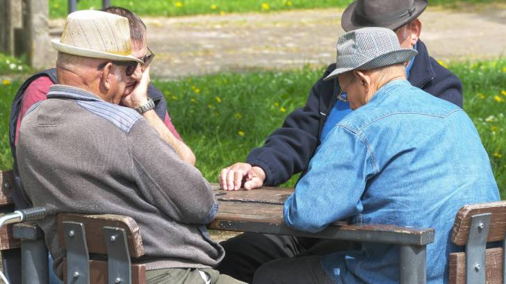 4 old men playing a game of dominos around a table outside