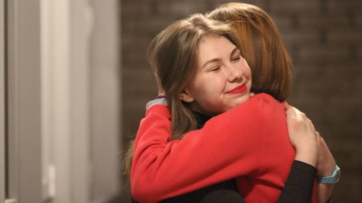 two women hugging, smiling