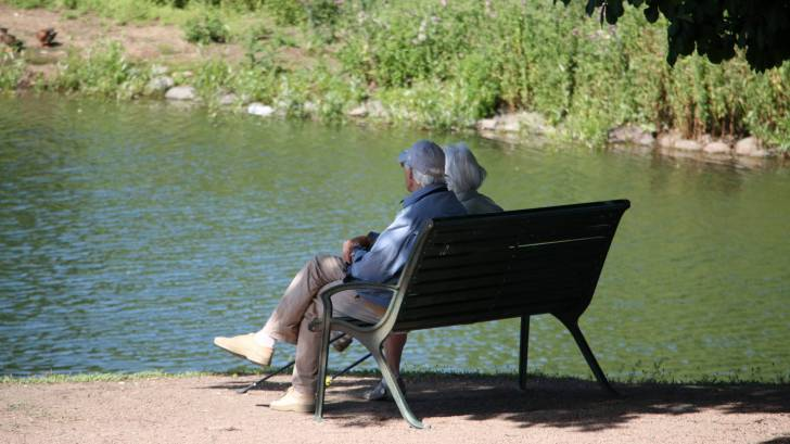 older people sitting on a bench by a lake
