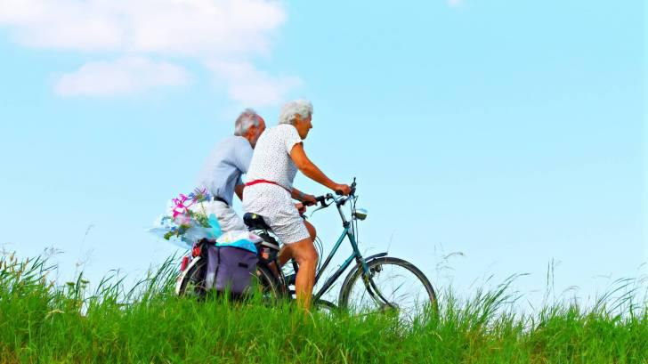older couple riding a bike under a beautiful sky