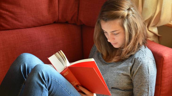 young girl reading book on sofa