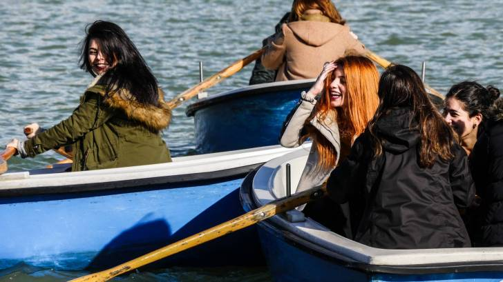 women friends in row boats laughing
