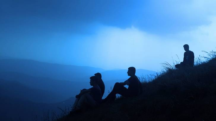 men sitting on a hill, silhouettes, looking for answers