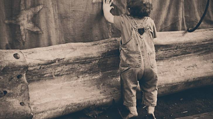 toddler looking through a fence