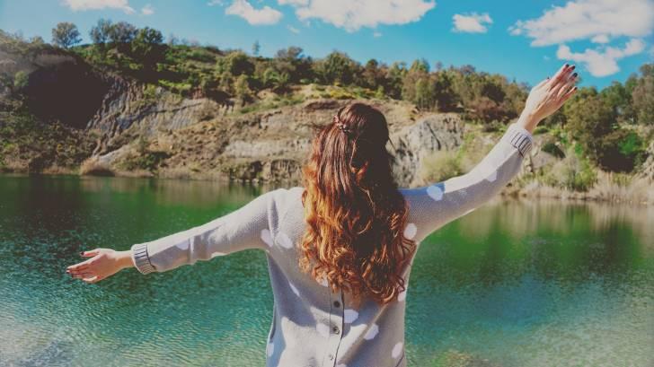 happy woman looking at a lake