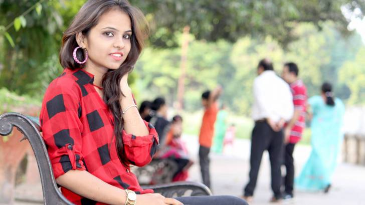 young woman an a park bench, family near by