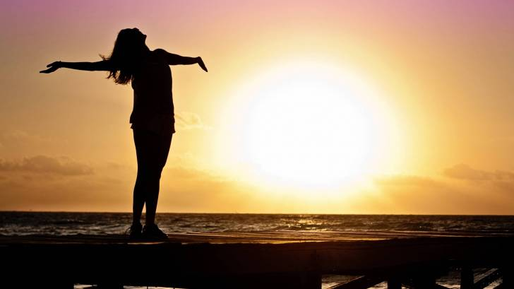 girl celebrating life with the sun coming up