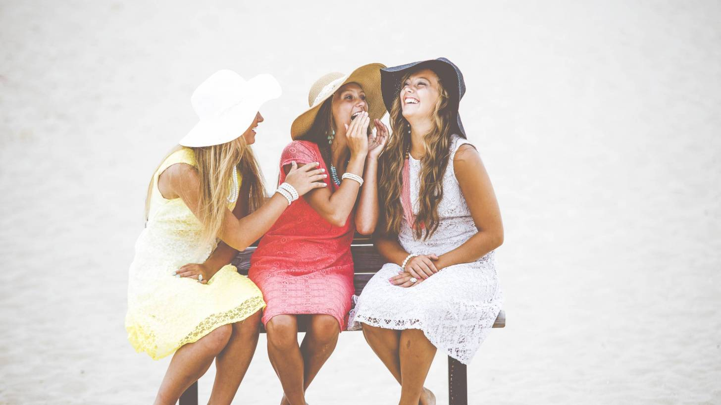 women sitting on a bench happy