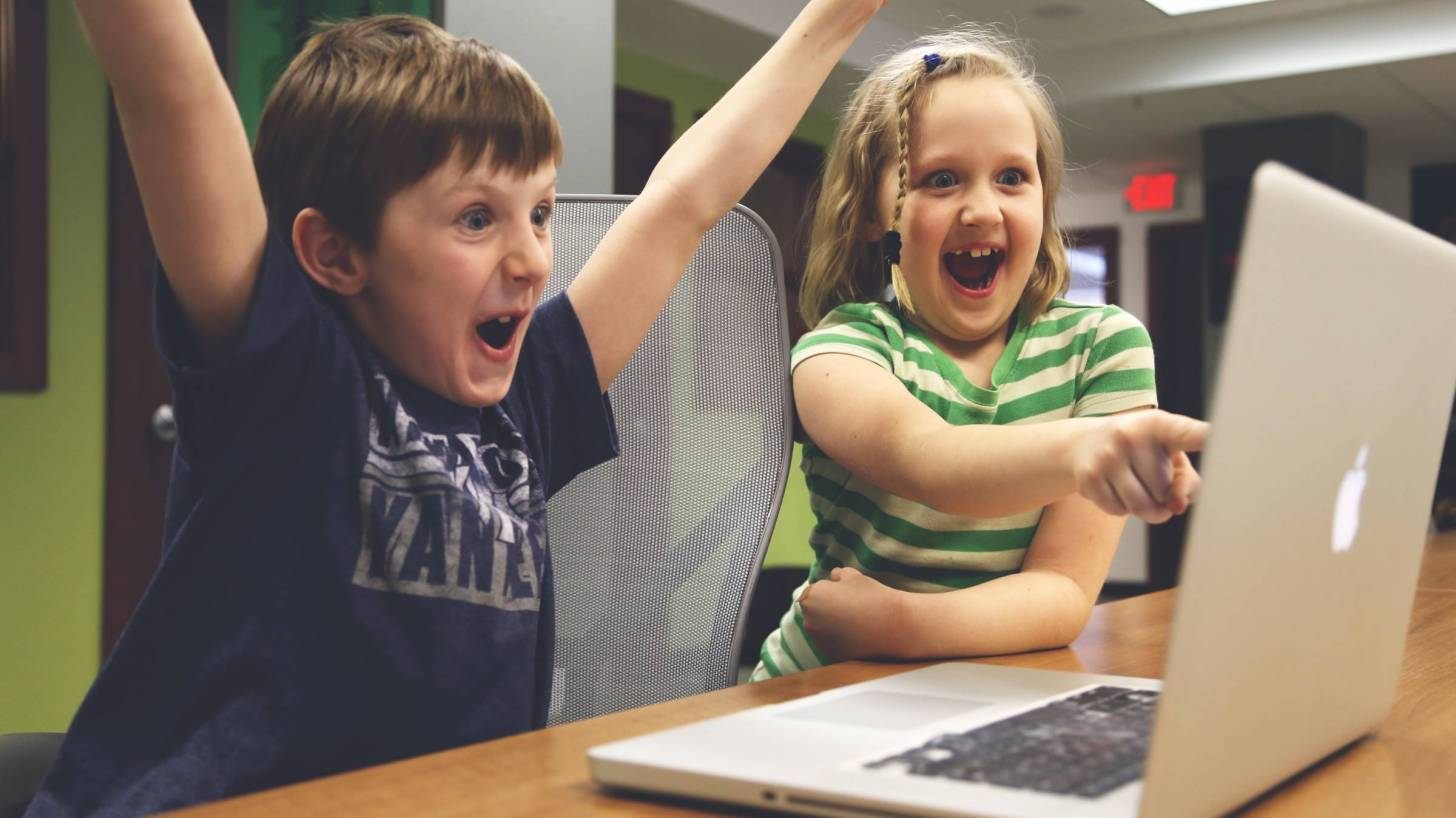 kids looking at a video on a computer screen