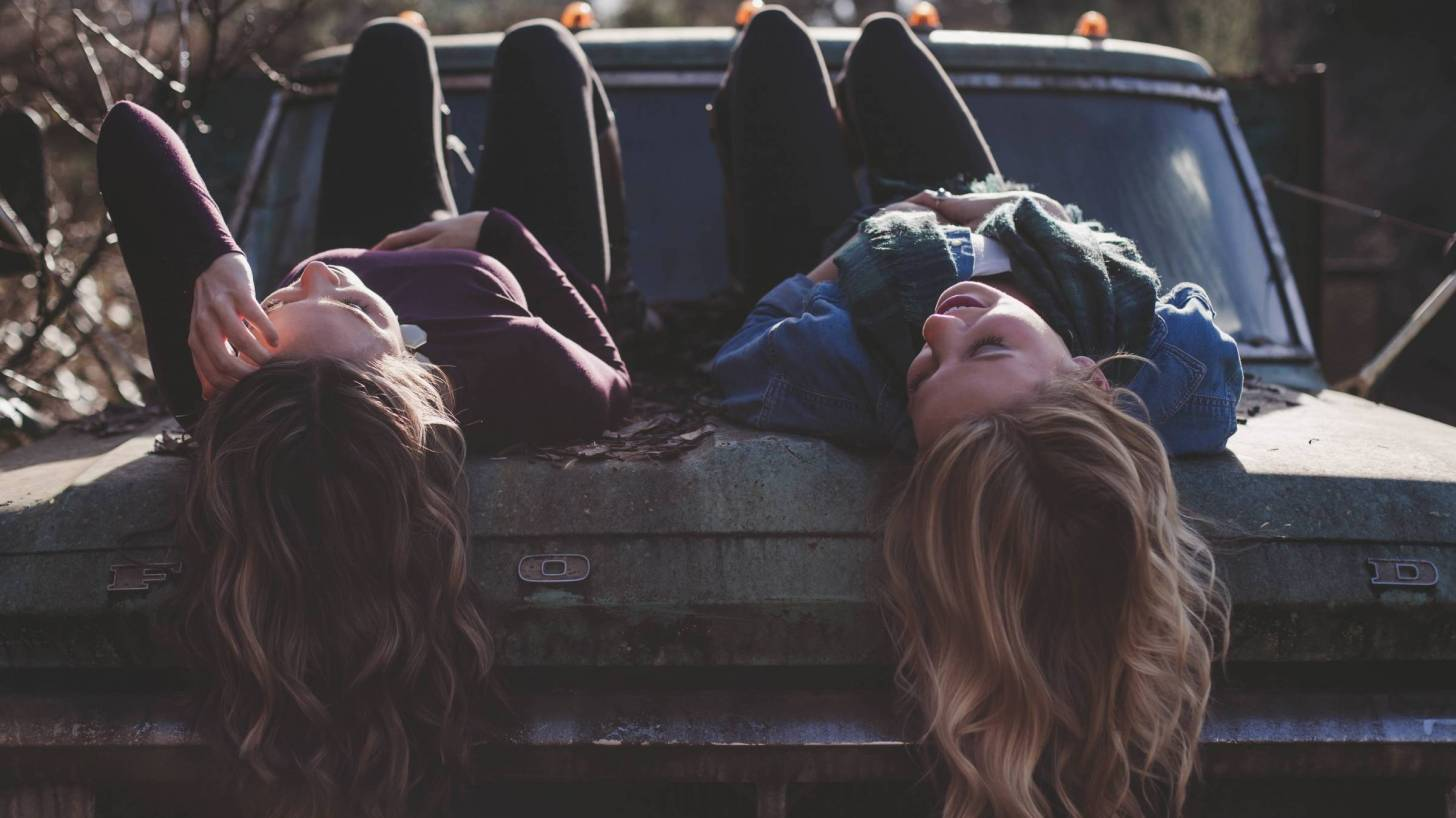 young girls lying on a car chatting