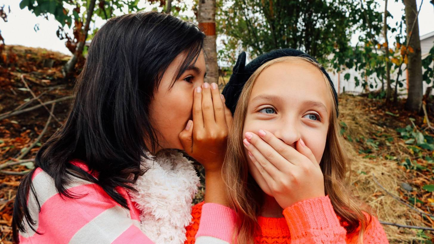 2 young girls telling secrets and whispering