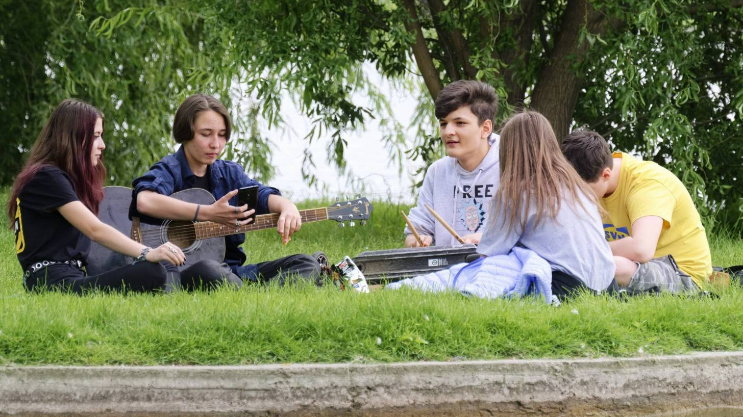 group of teens sitting in a circle outside