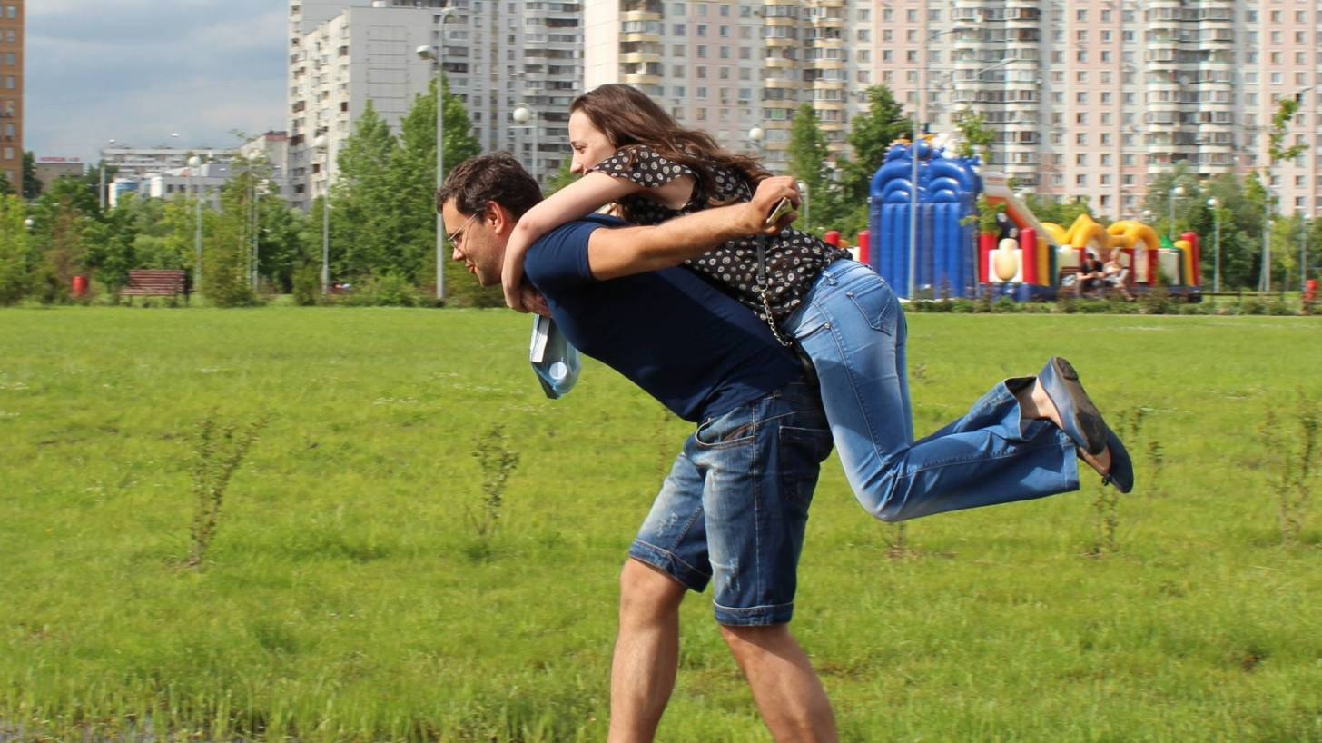 man carrying female on his back helping