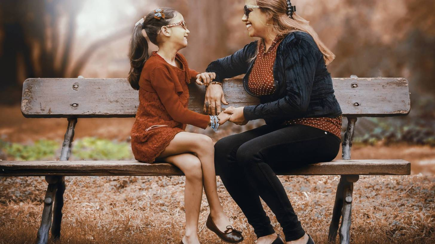 mom and daughter talking on a park bench