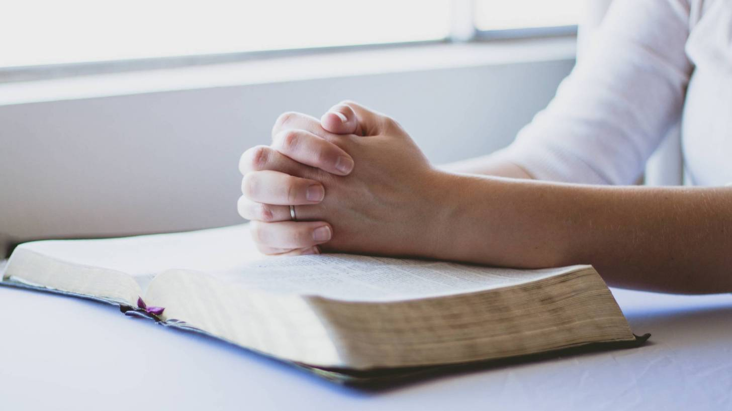 hands folded on a bible saying prayers