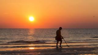 man on beach hunting for treasure