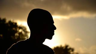 profile of man looking at a sunset