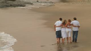family of adults walking on a beach