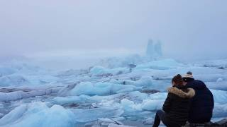 couple sitting on the edge of an iceberg