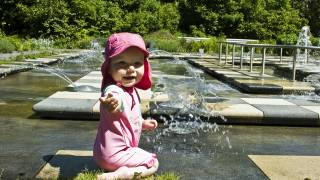 young happy girll baby playing in water