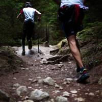 men running up a rocky hill