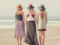 three young women string at the ocean