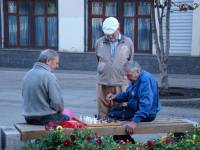 older men playing chess in a park