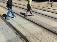 two older men walking across the street
