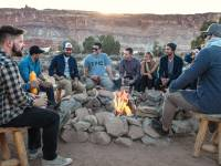 group of people sitting around a camp fire