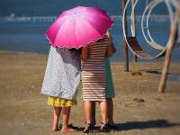 women on a beach protecting from the sun with an umbrella