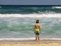 young boy looking at the ocean surf